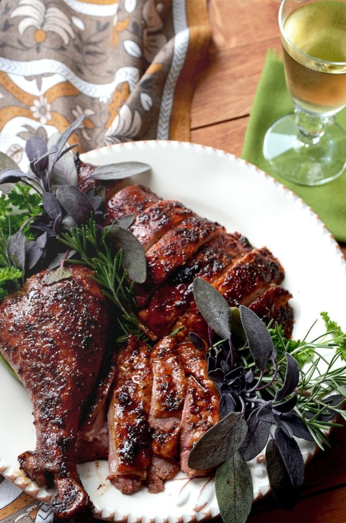 Brown Sugar Date Roast Turkey cut up on a white serving platter garnished with herbs.