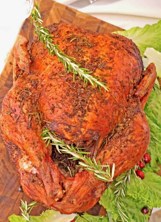 Roasted turkey with citrus and herb garnishes.