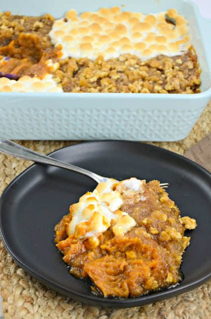 A large serving of sweet potato casserole on a black plate.