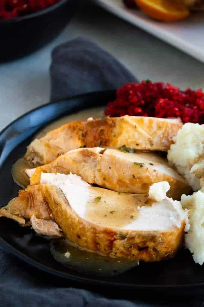 Sliced turkey breast with cranberry relish on the side.
