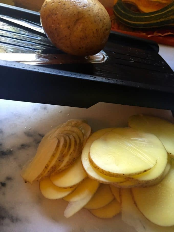 Slicing potatoes on a mandoline for Ultimate Blue Cheese Au Gratin Potatoes