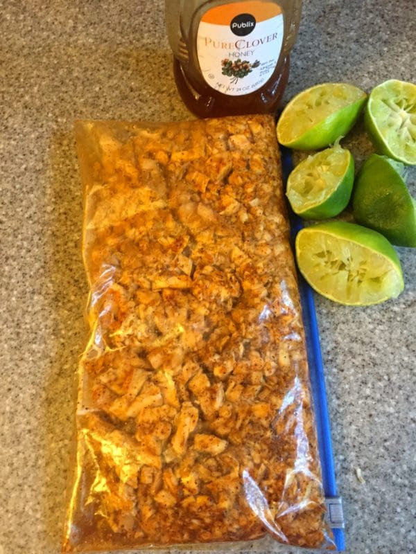Turkey in a storage bag with the marinade, squeezed limes, and pure clover honey on the counter.