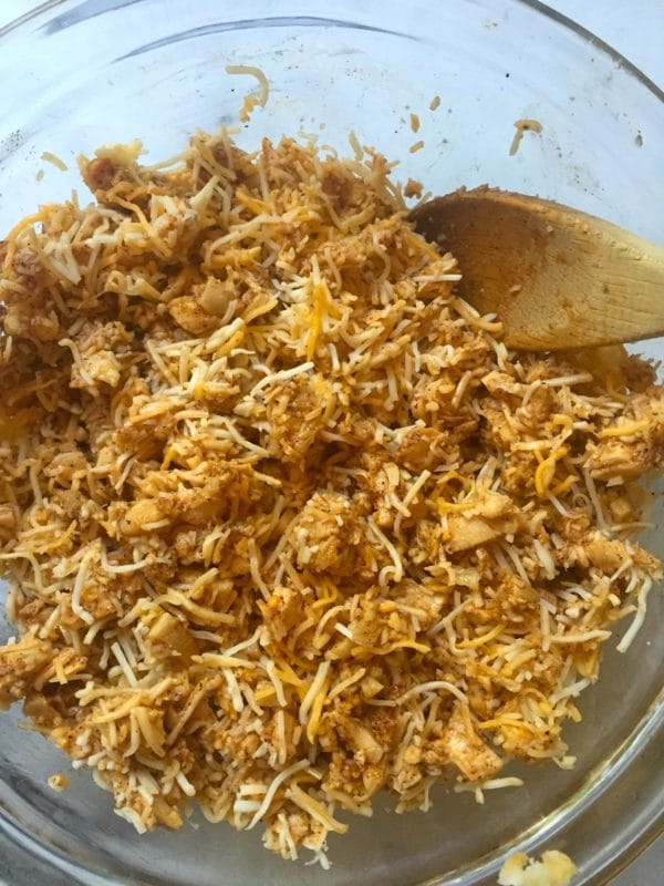 Marinated turkey with shredded cheese in a glass bowl with a wooden spoon.