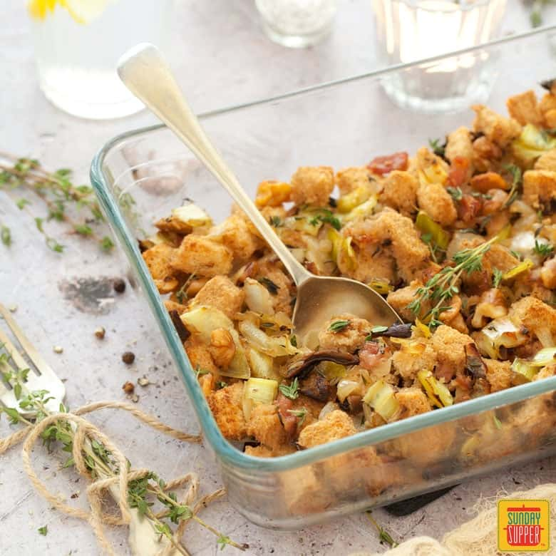 Gluten free stuffing in a clear glass baking dish.
