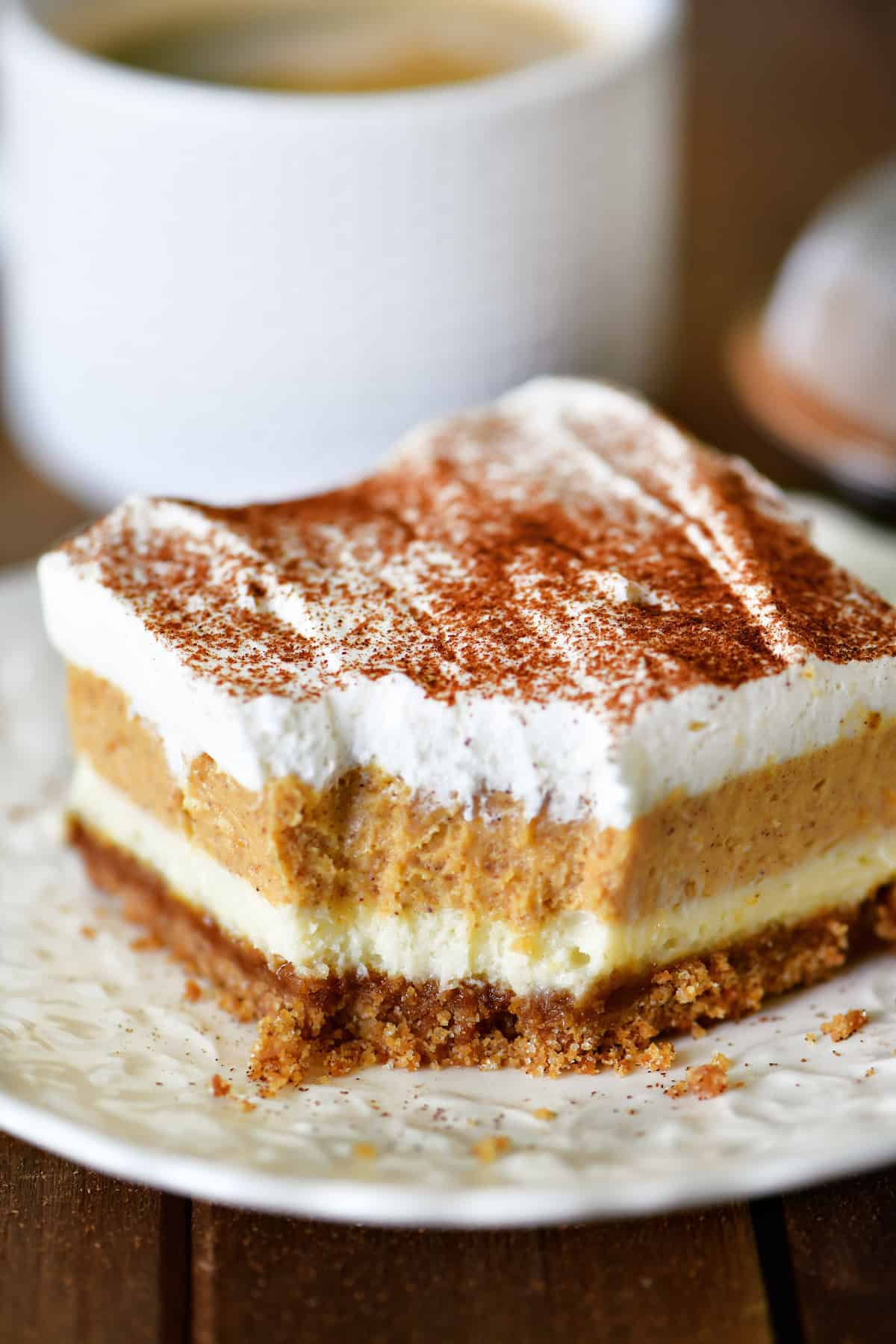 A slice of Pumpkin Cheesecake Dessert on a white plate.