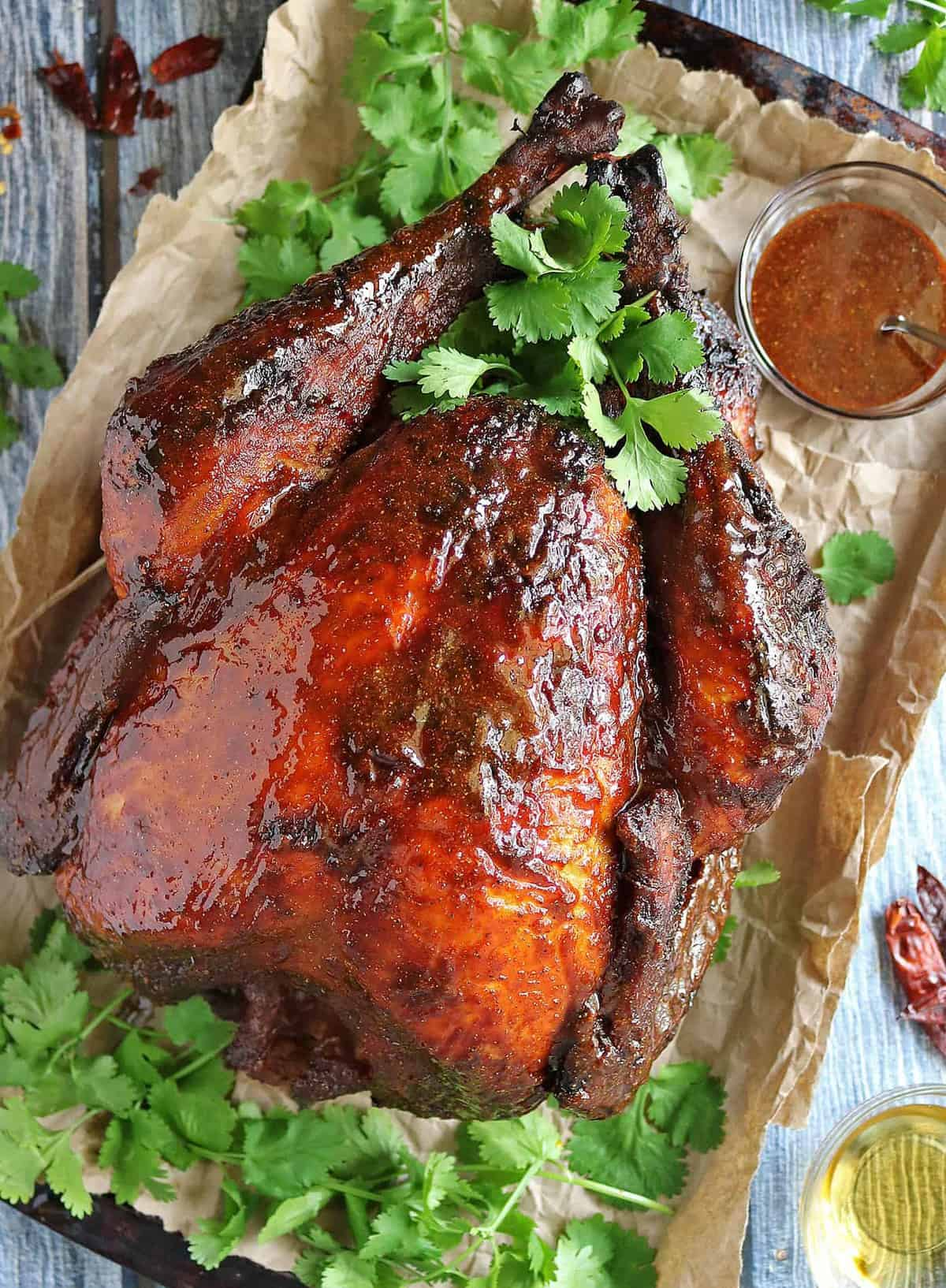 A baking sheet covered with a brown paper bag holding a large honey glazed cooked turkey.
