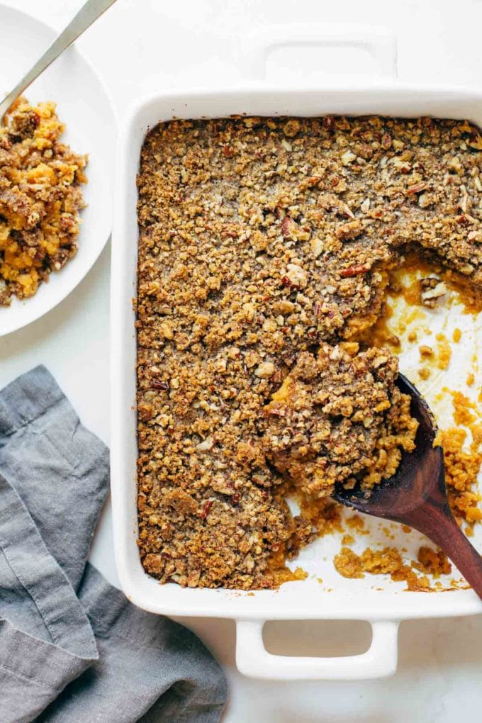 Sweet potato casserole in a white baking dish with a wooden spoon.