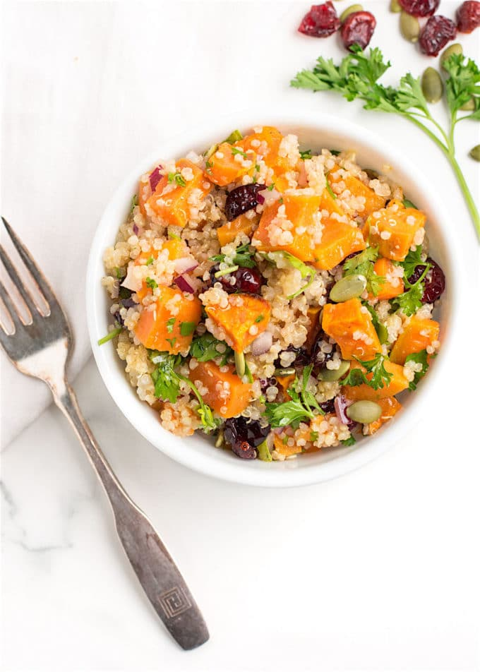Sweet potato quinoa salad in a white bowl with a fork.