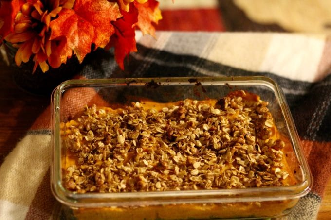 Lightened up sweet potato casserole in a glass baking dish with autumn leaves next to it.