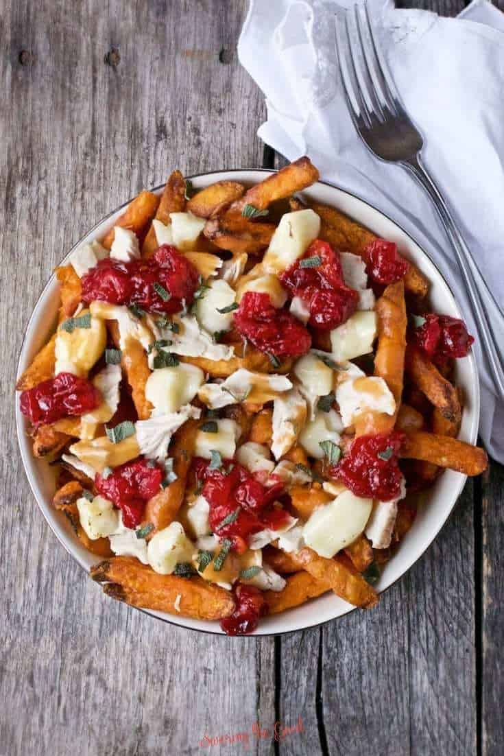 Thanksgiving Poutine made with leftovers in a bowl on a wooden board.