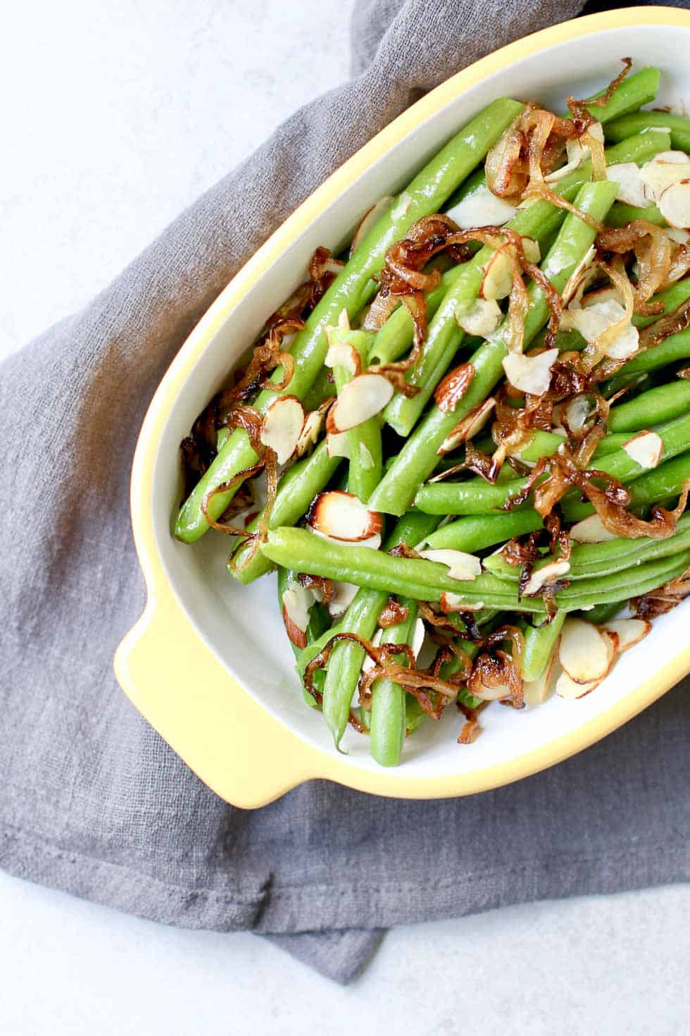 A gratin dish full of cooked green beans and almonds.