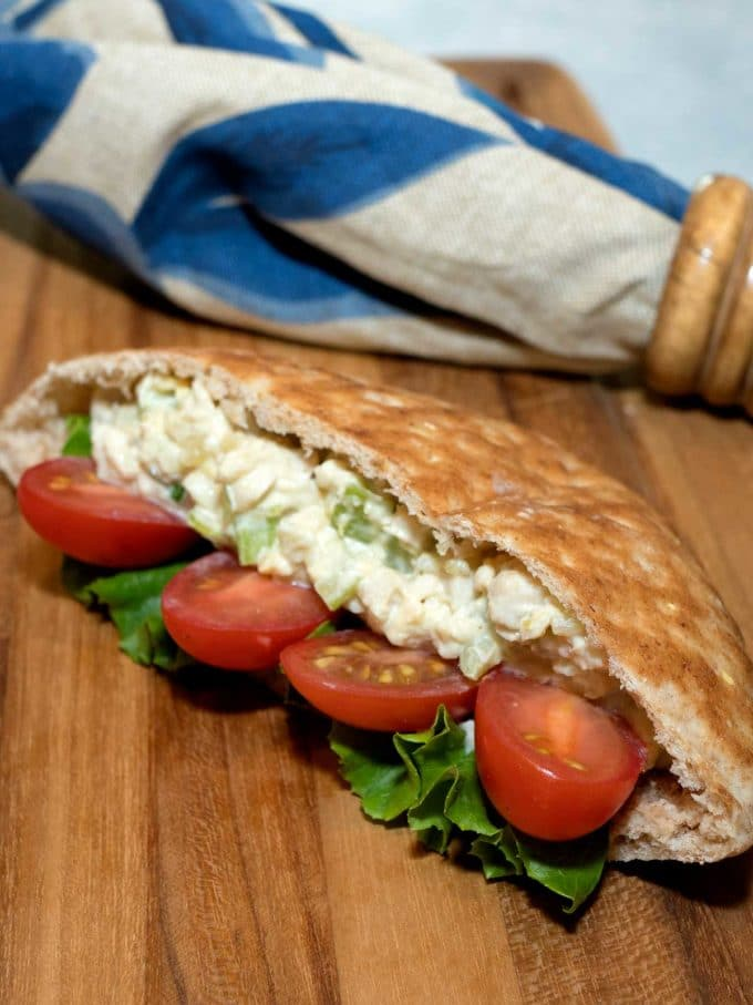 Pita pockets full of turkey salad and sliced tomatoes.