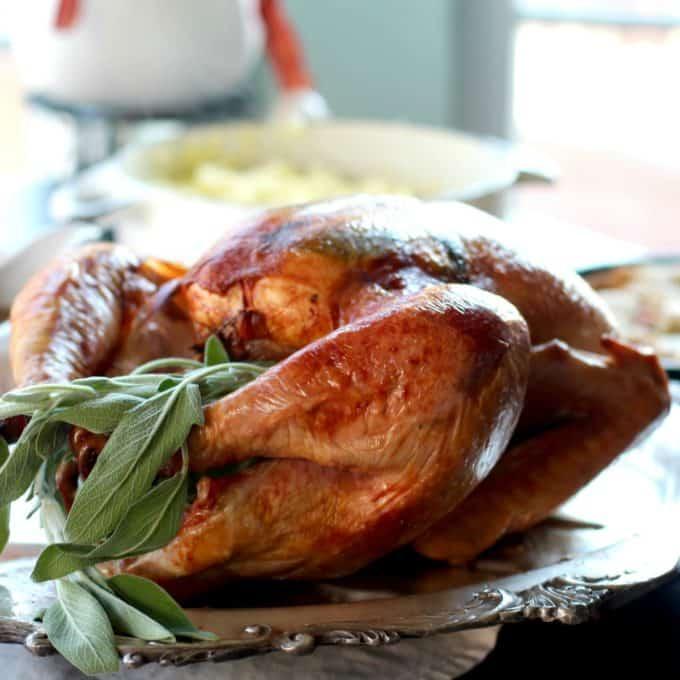 Large roasted turkey on a platter garnished with sage leaves.