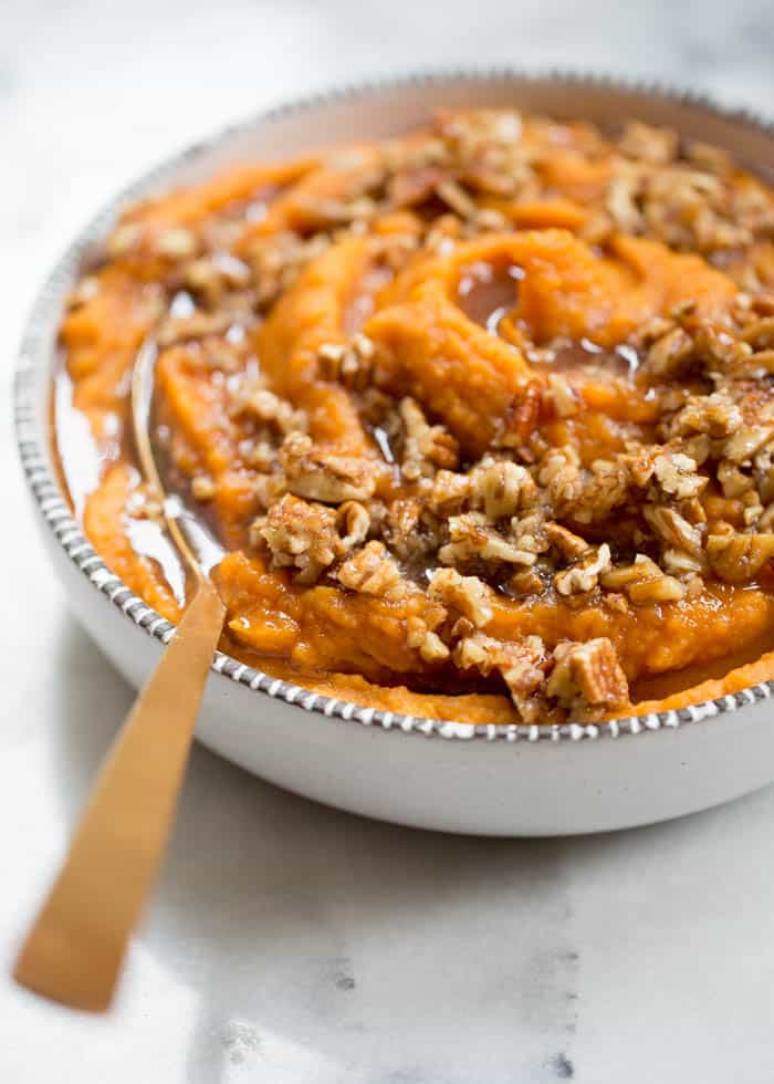 Coconut Whipped Sweet Potatoes in a bowl topped with maple syrup and pecans.