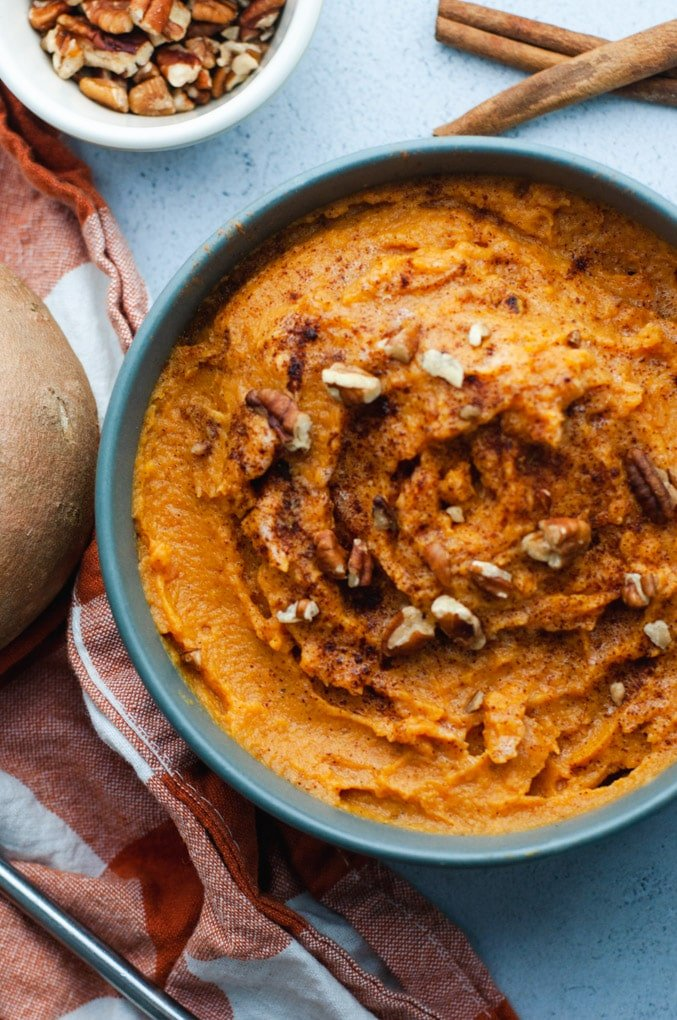 A blue bowl full of mashed sweet potatoes topped with cinnamon.