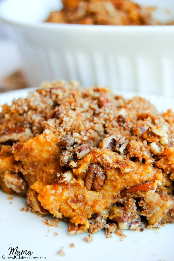 A large serving of sweet potato casserole topped with pecans on a white plate.