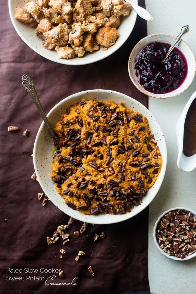 Paleo Sweet Potato Casserole in a white bowl next to a bowl of cranberry sauce.