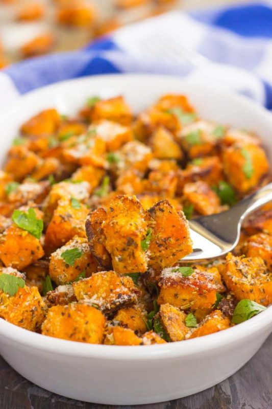Parmesan Sweet Potato Cubes in a bowl garnished with parsley.