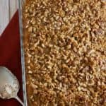 A large baking dish full of sweet potato casserole topped with pecans and brown sugar.