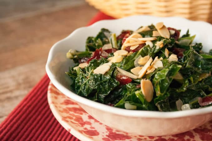 Thanksgiving Kale in a white glass bowl topped with chopped almonds.