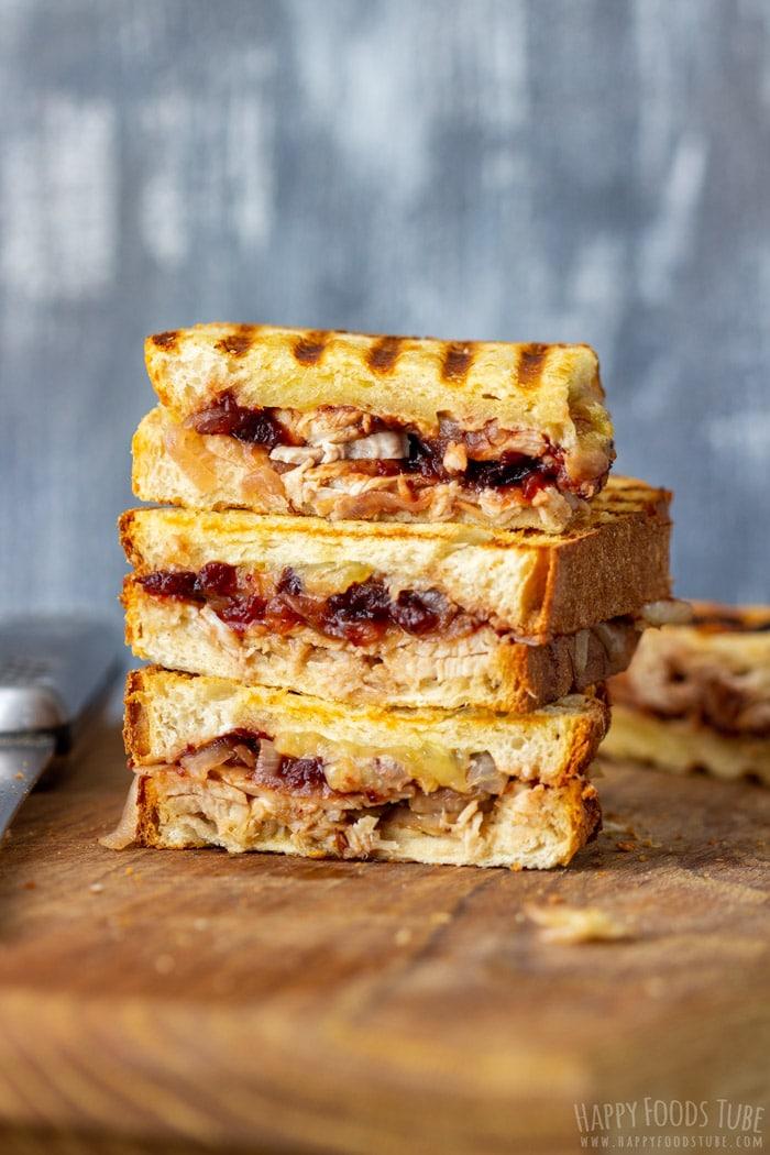 Turkey Cranberry Panini Sandwich on a wooden cutting board.