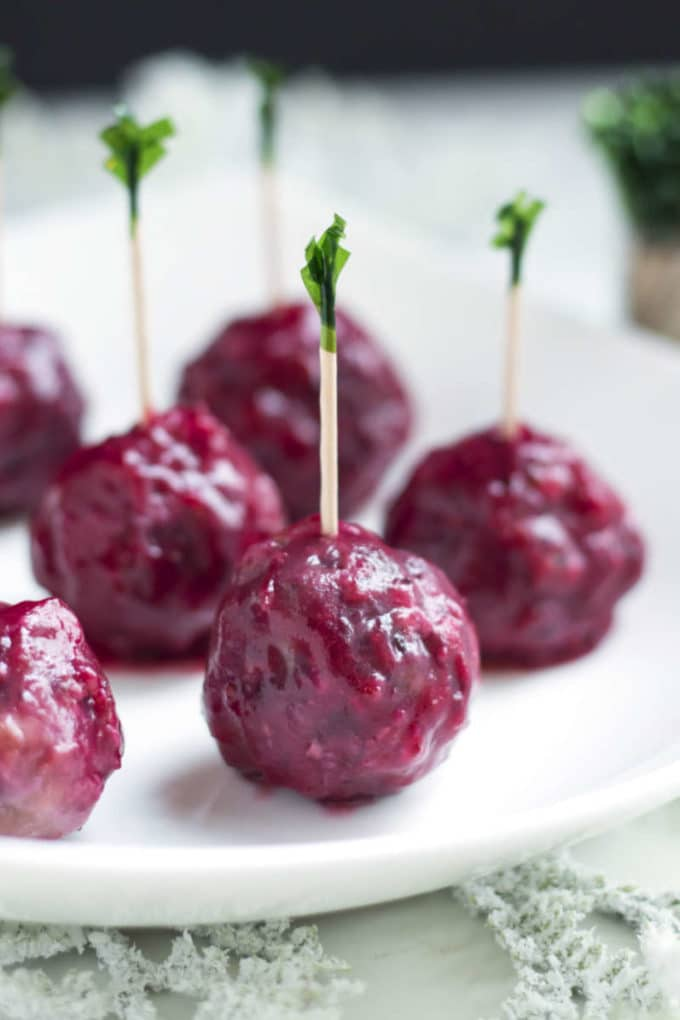 Cranberry sage meatballs with cocktail picks on a white plate.