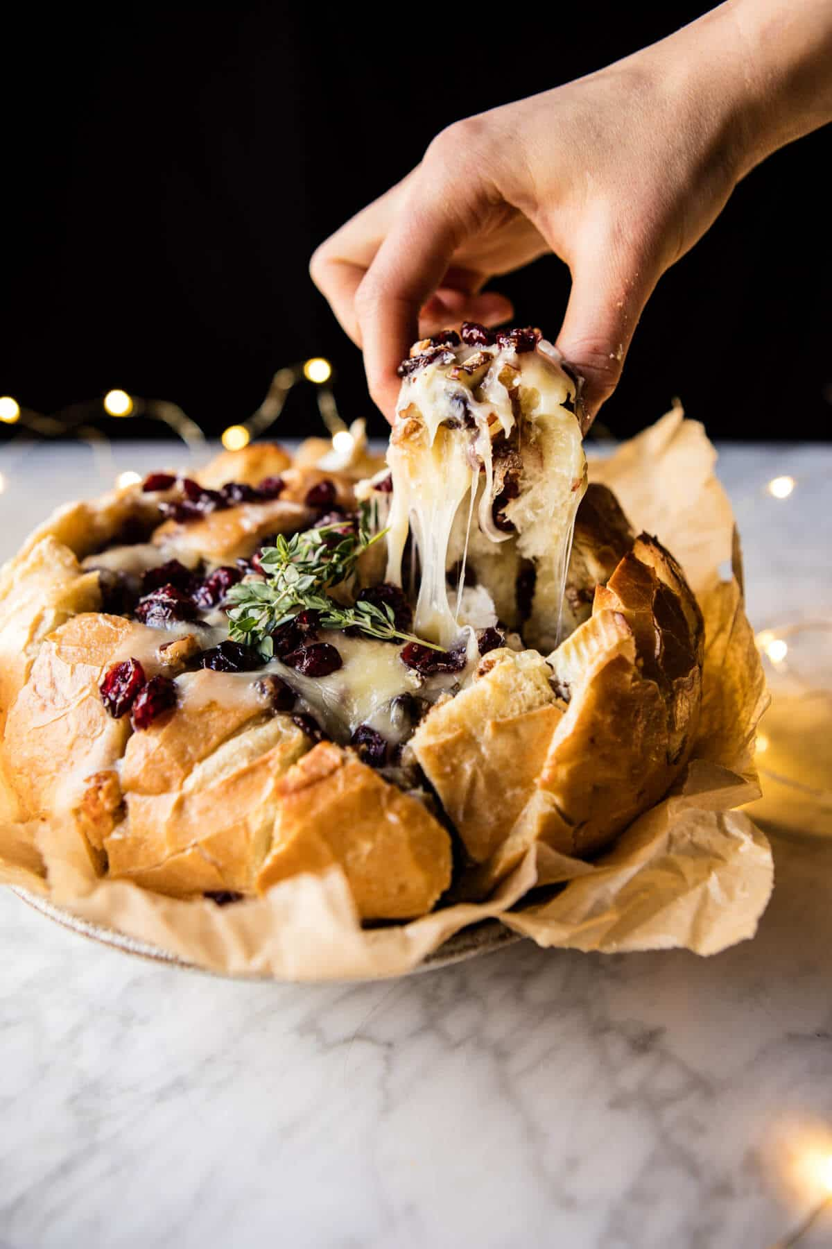 Cranberry brie pull apart bread with a hunk being pulled out.
