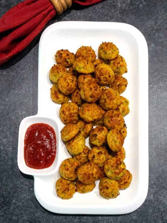 Easy cheesy zucchini bites on a white plate with catsup.