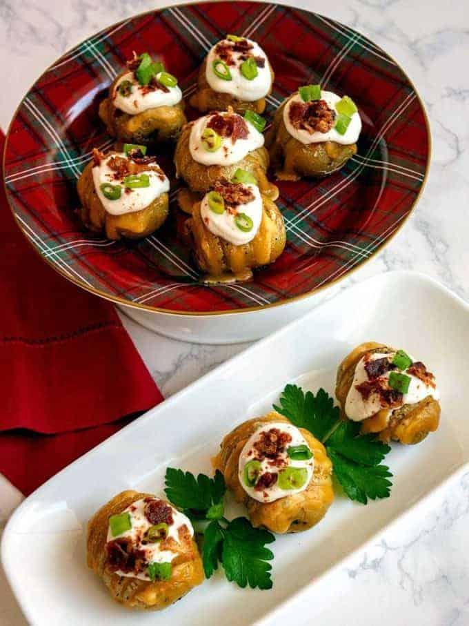 Loaded mini hasselback potato bite appetizers on a serving platter.
