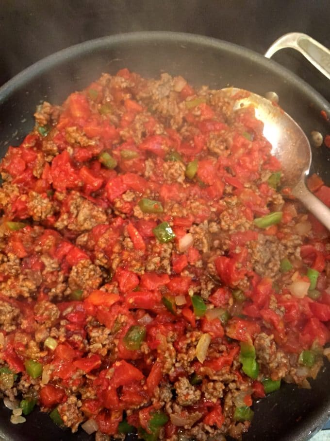 Adding tomatoes to the cooked beef mixture for Beef and Tomato Skillet with Polenta