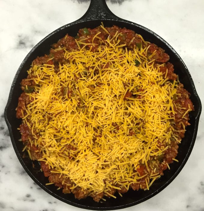 Adding a cheese topping to Beef and Tomato Skillet with Polenta before it is baked
