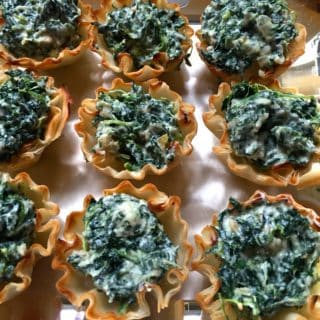 Nine Spinach and Goat Cheese Tartlets on a white cloth.