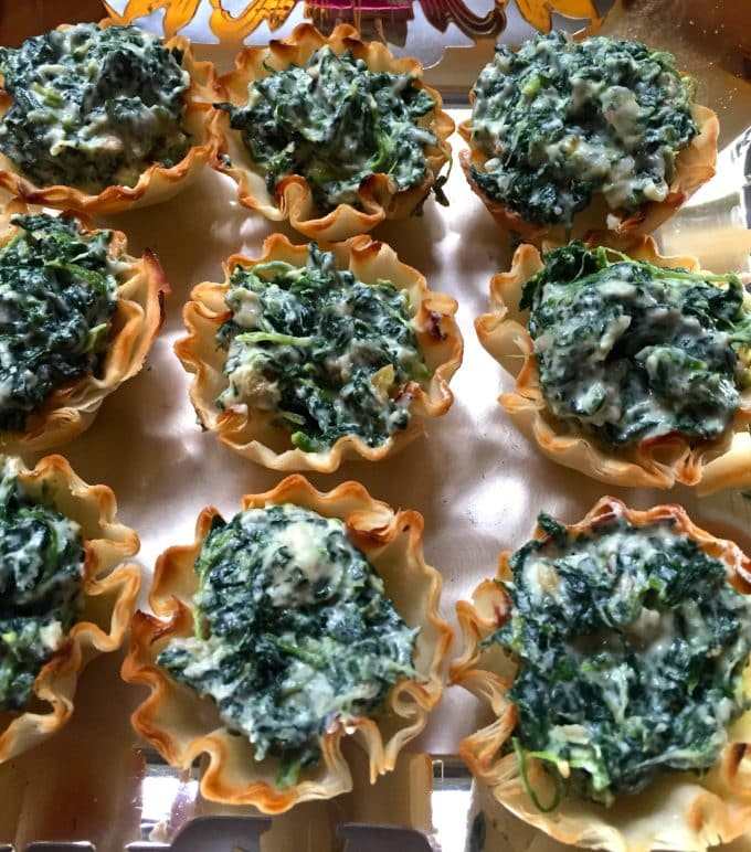 Baked phyllo shells filled with a spinach mixture on a serving platter.