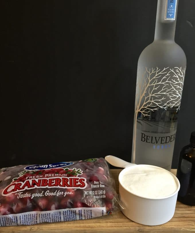 A bottle of vodka, cranberries, sugar and vanilla on a cutting board.