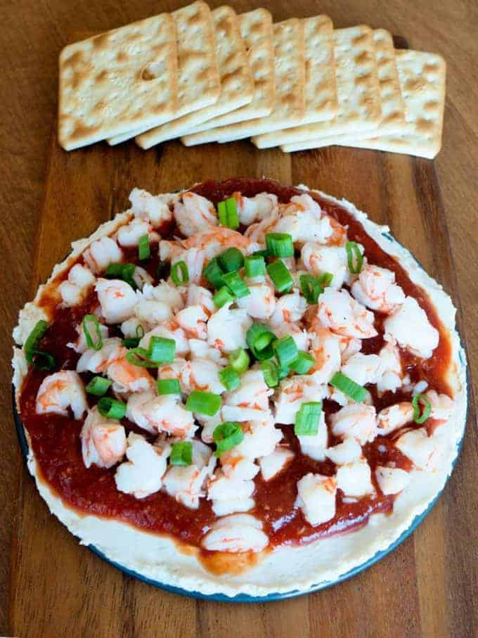 Layered shrimp spread with chopped shrimp on a white plate.