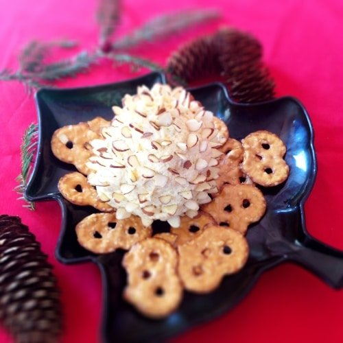Pinecone cheese spread appetizer stuffed with sliced almonds on a Christmas tree shaped plate with crackers.