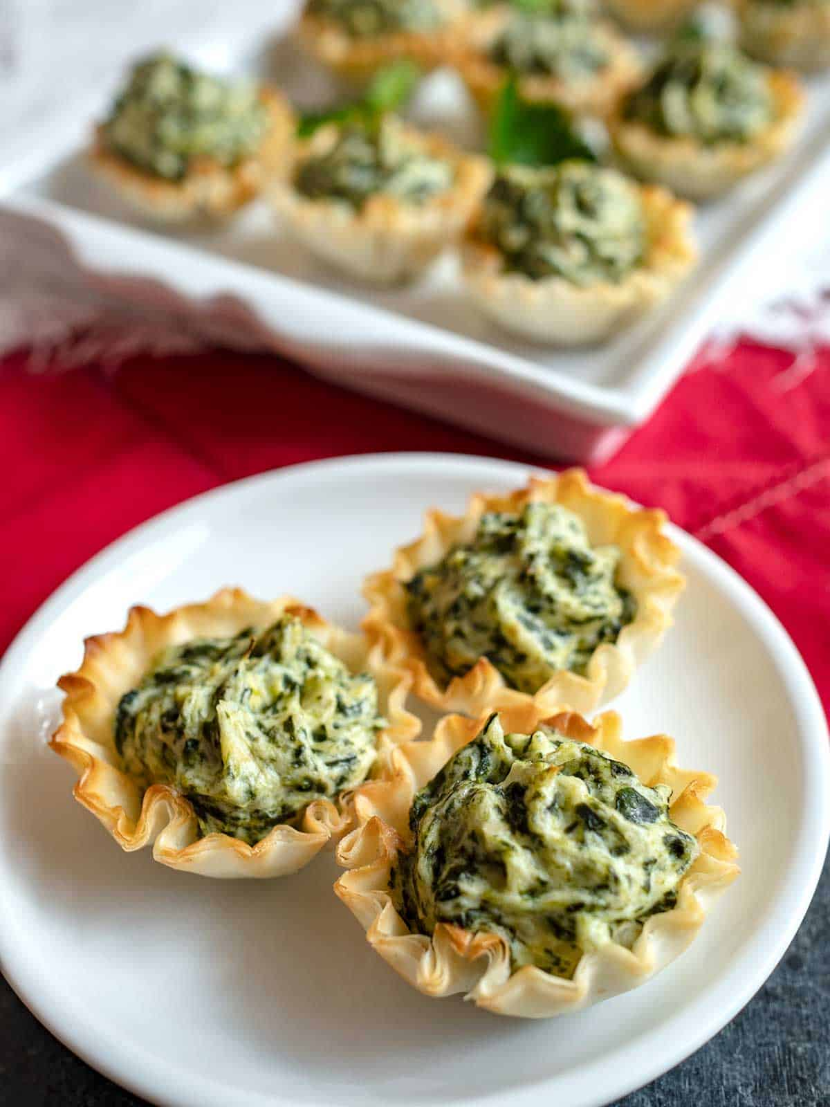 Three spinach artichoke tartlets on a white plate.