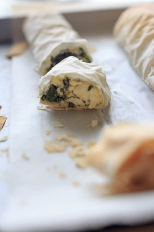 Spinach phyllo roll-ups cut up on a piece of parchment paper.