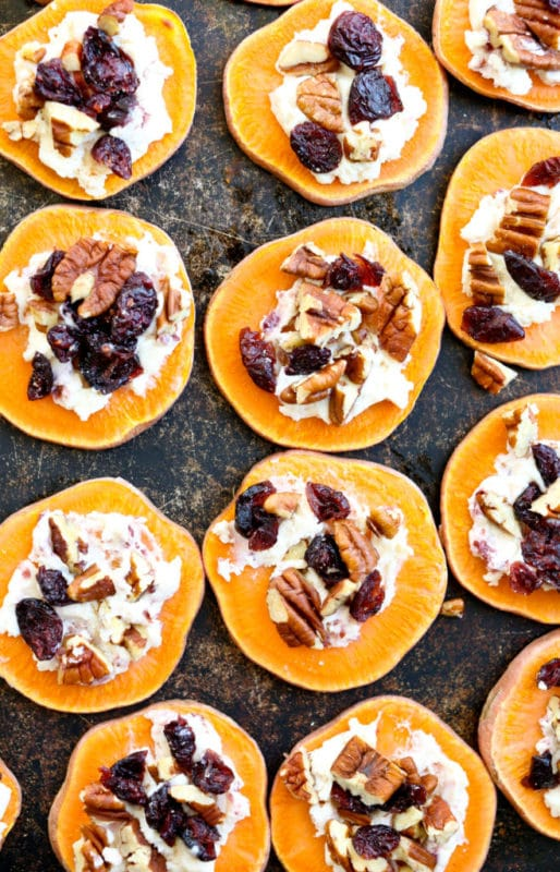 Sweet potato toasts with cranberries and nuts on a baking sheet.
