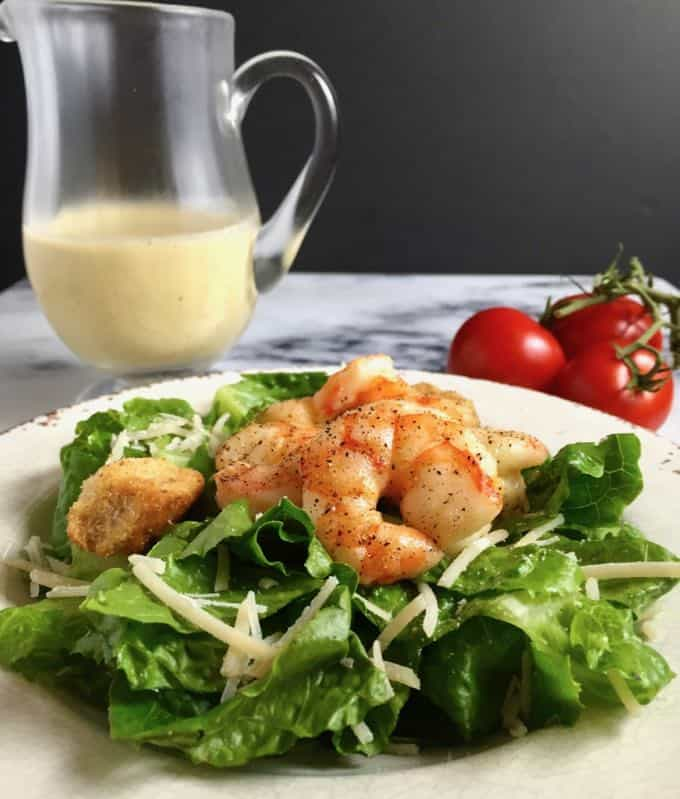 Caesar salad with roasted shrimp on a white plate.