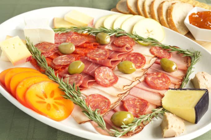 A charcuterie board made with meat and cheese in the shape of a Christmas tree.