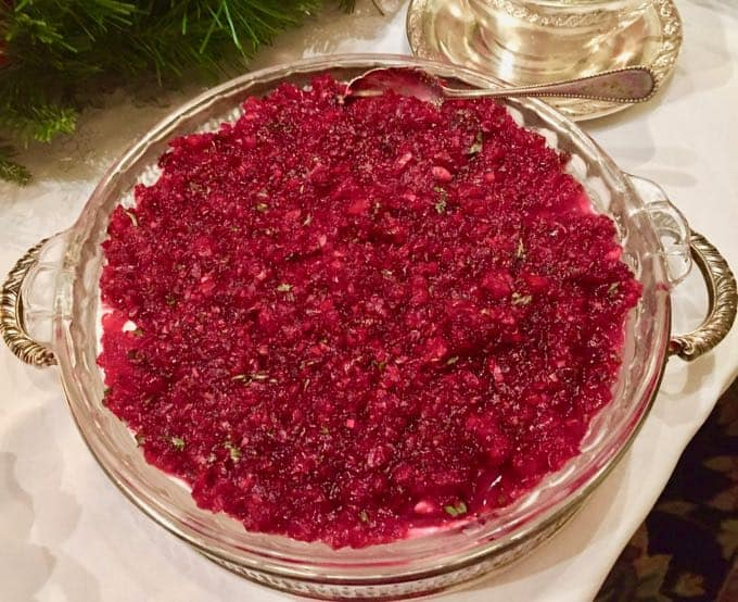 A silver serving dish with cranberry jalapeno cream cheese dip.