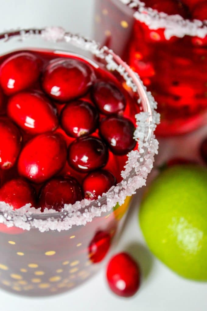 Cranberry margaritas in a glass with sugar on the rims.