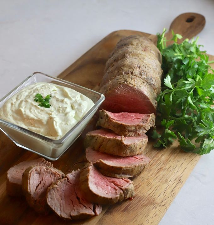 Perfect Beef Tenderloin with Gorgonzola Sauce ready to serve on a cutting board.