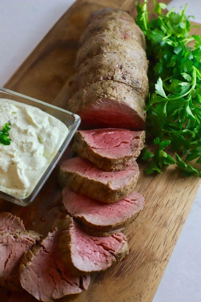 Perfect Beef Tenderloin with Gorgonzola Sauce on a cutting board garnished with parsley