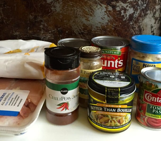 Ingredients for soup including chicken, chili powder, canned tomatoes, garlic and corn.