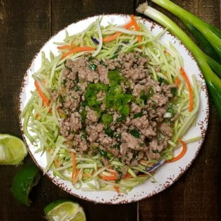 Thai Pork with Asian Slaw on a plate with scallions and cut limes on the table.