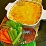 Buffalo Chicken Dip in a small baking dish with celery, carrots, and triscuits on the side.