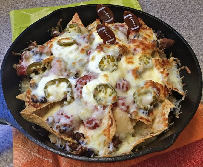 Skillet Macho Nachos in a cast iron skillet topped with cheese and jalapeno slices.