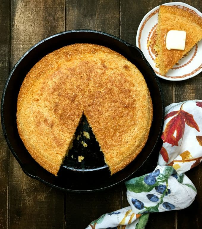 Cornbread in a cast-iron skillet with a slice on a small plate.